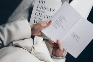 a woman dressed in white holding a book with essays and poems