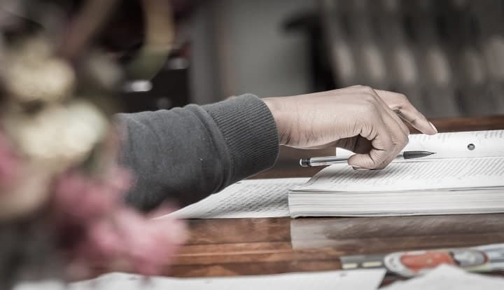 person putting a pen on a book