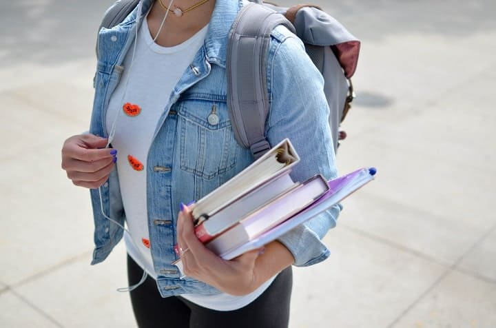 student girl holding a stack of books and papers