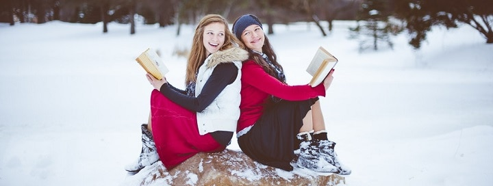 two happy women on a rock holding books