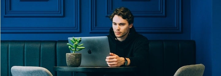 person sitting at a table with a laptop