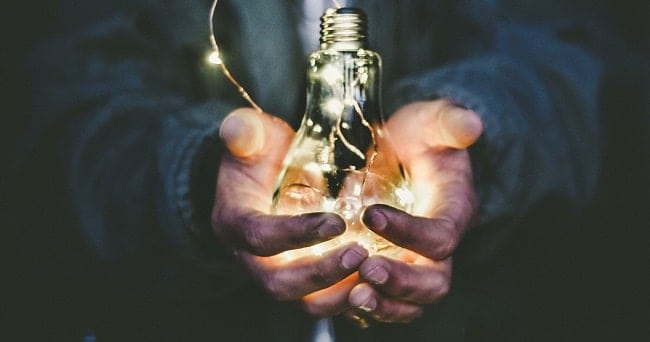 a person holding an idea lightbulb in their hands