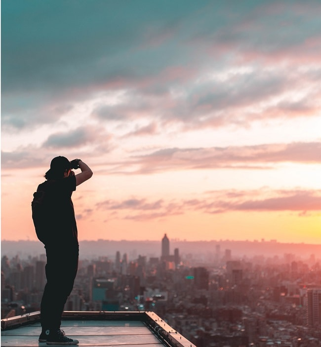 man standing on a building and taking a picture