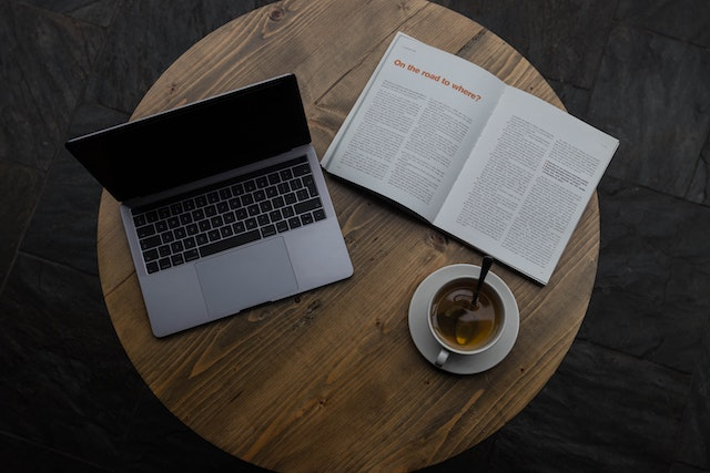 A reading table with a laptop and a print magazine